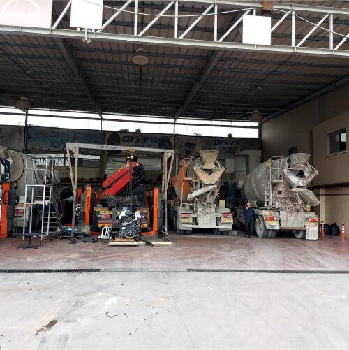 מרכז שירות מורשה למשאיות באשקלון - מבט מבחוץ למוסך שם עומדות משאיות שמקבלות שירות מימין לשמאל שני מערבלי בטון משאית על ליפט ועוד משאית