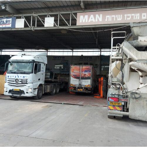 מרכז שירות מורשה למשאיות מבט מבחוץ על משאיות שנמצאות במוסף ומקבלות שירות