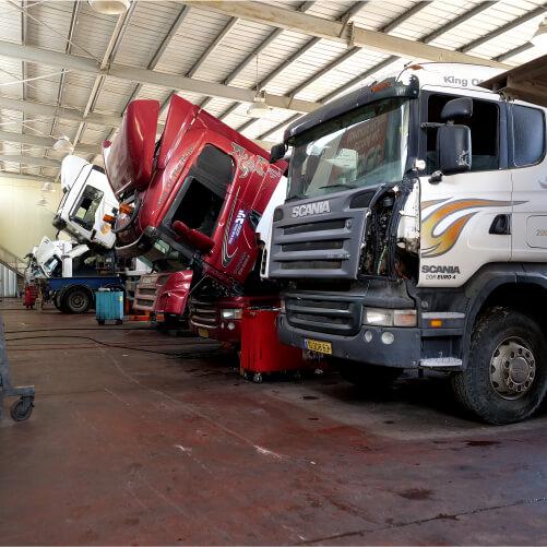 שלוש משאיות עומדות במוסך במרכז שירות מילניום ומקבלות טיפל משאית ראשונה לבנה שניה אדומה ועוד אחת לבנה על משטח אדום